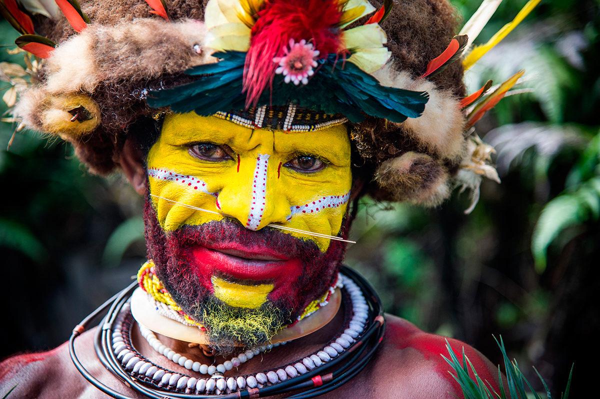 Мужчина племени в традиционной одежде и раскраске лица