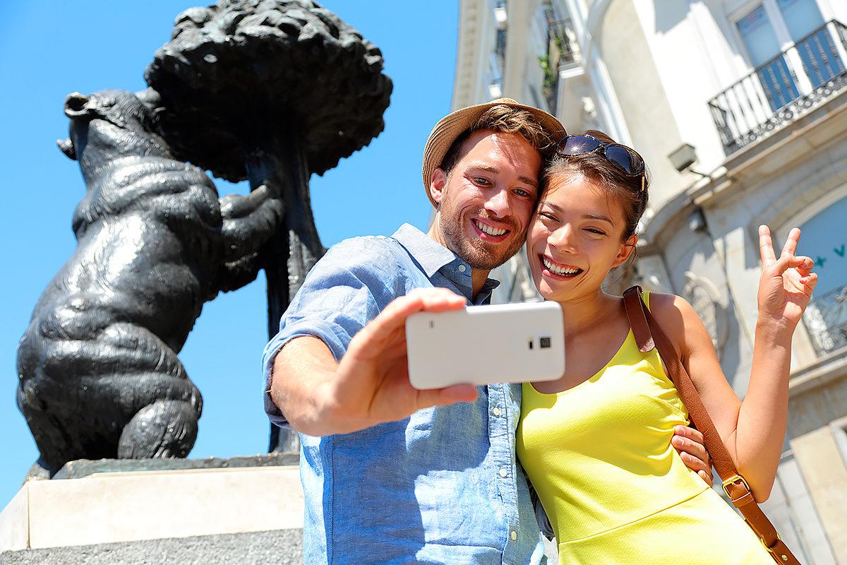 Туристы на фоне статуи медведицы